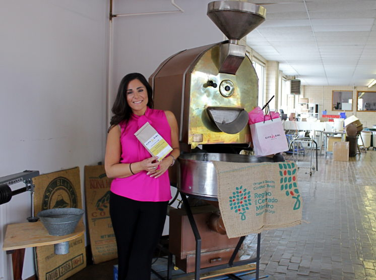Alyza Bohbot poses in front of Alakef's original roaster with City Girl Coffee swag