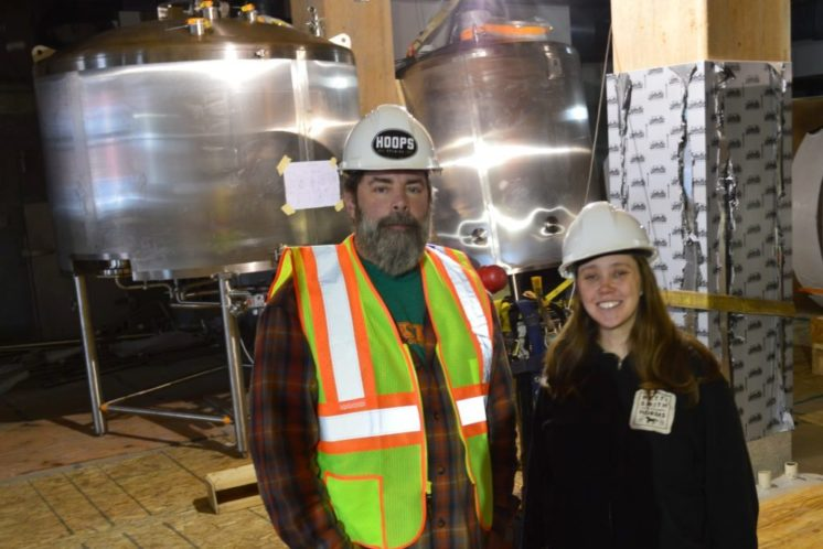 Hoops Brewing founder Dave Hoops and Head Brewer Melissa Rainville pose in front of recently installed beer kettles. Hoops Brewing plans to open in late May or June.